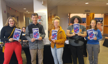 Five students holding fliers at National Portfolio Event