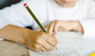 Kid writing with pencil