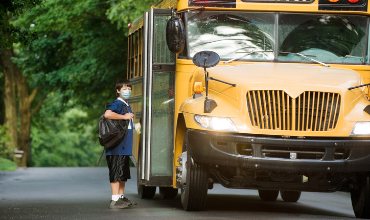 Boy in mask with school bus