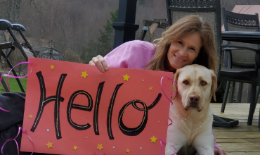 Woman outside with dog and sign that says hello
