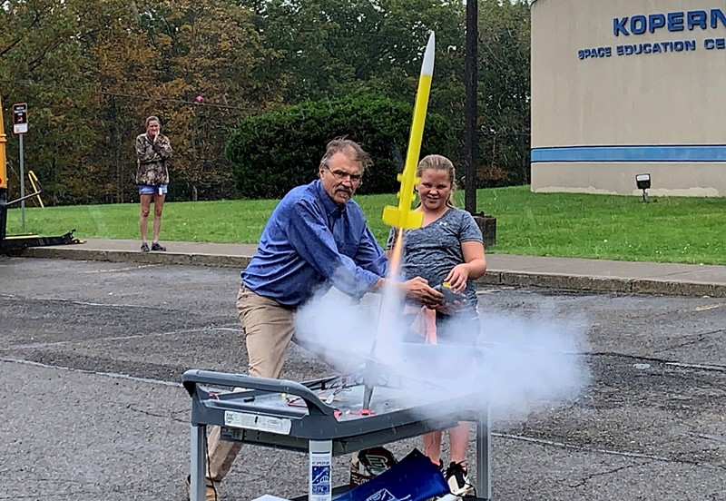 Student launches a rocket with help from man outside