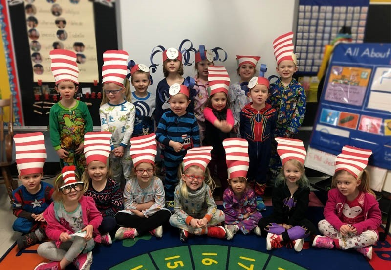 Group of pre-k students in classroom wearing striped paper hats