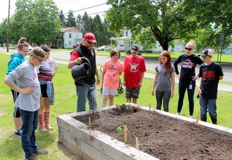 Students and teachers gather around garden