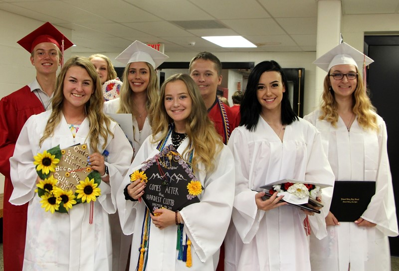 Eight students in caps and gowns
