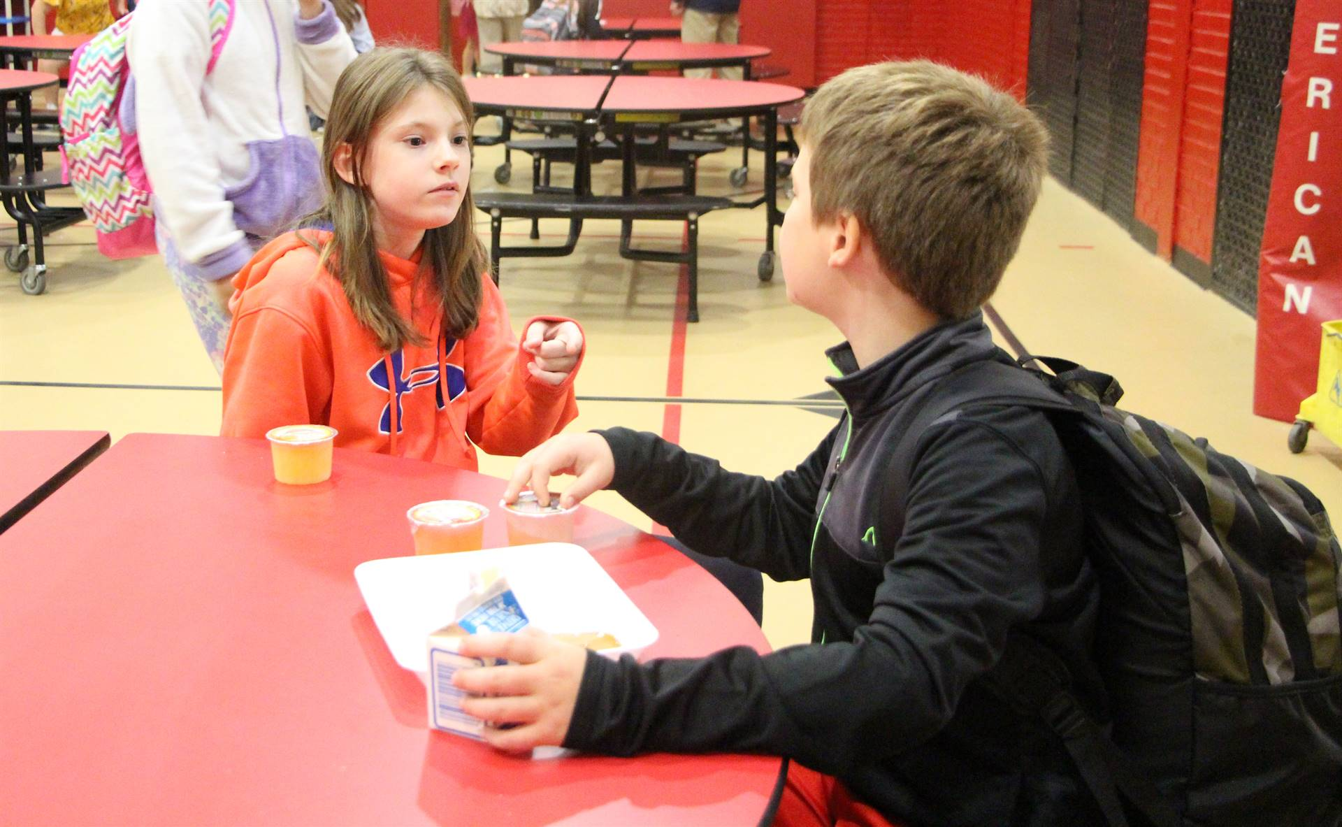 Girl and boy talking in cafeteria