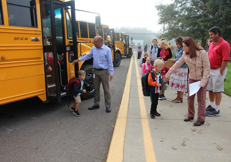 Principal helps students off bus