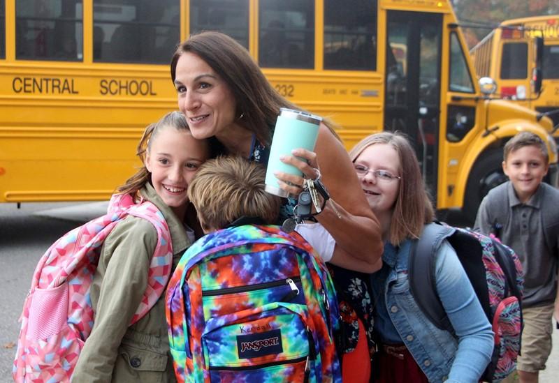 Teacher hugs students