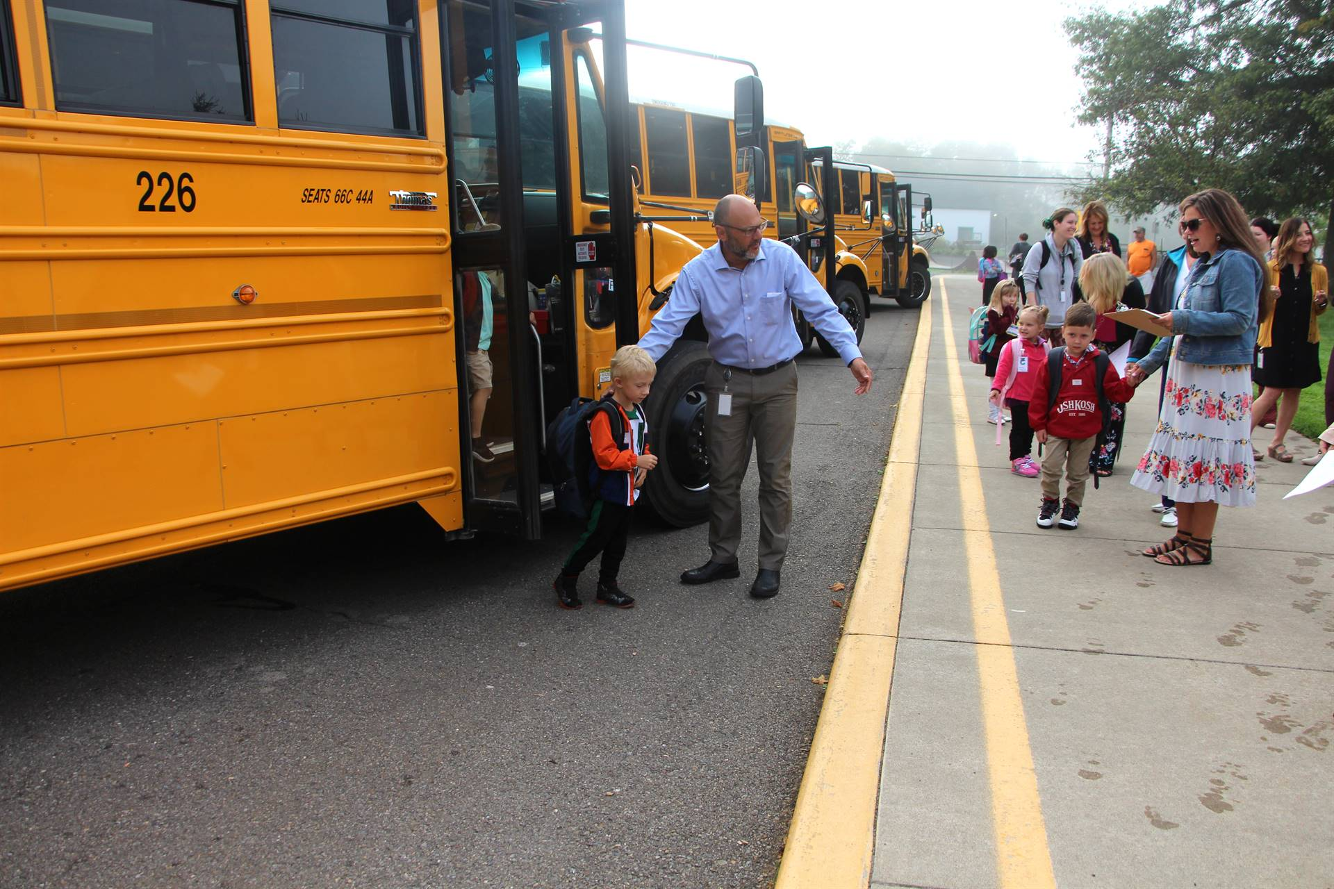 Principal helps boy off bus