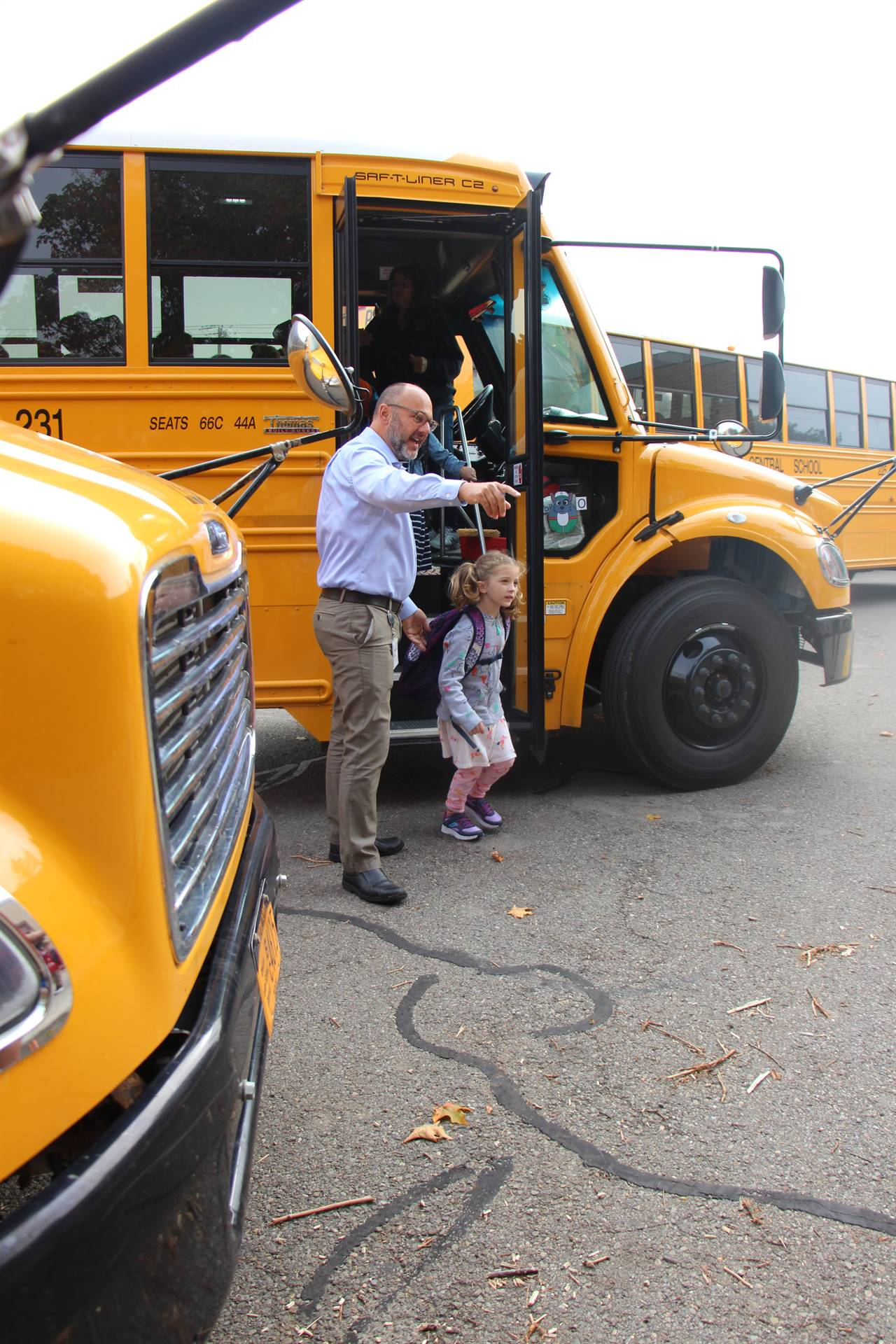 Principal helps girl off bus