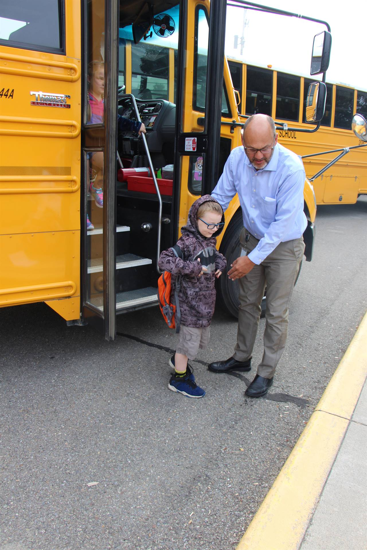 Principal helps student off bus