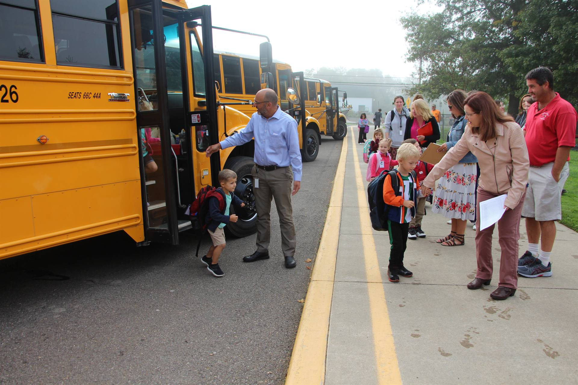 Principal helps students off bus