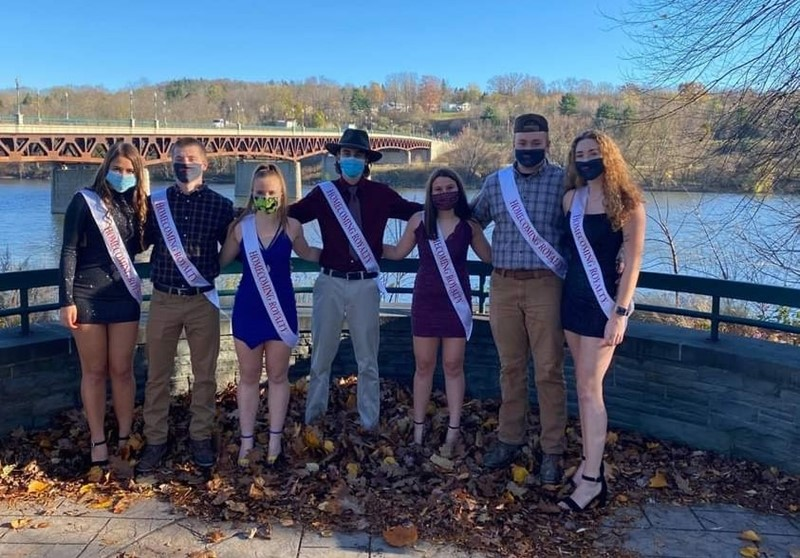 Seven students stand together outside near bridge