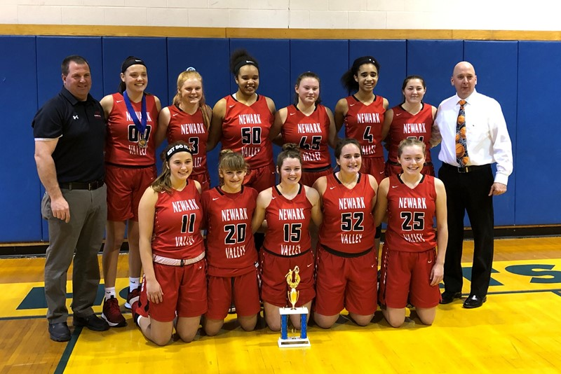 Girls basketball team with coaches in gym with trophy