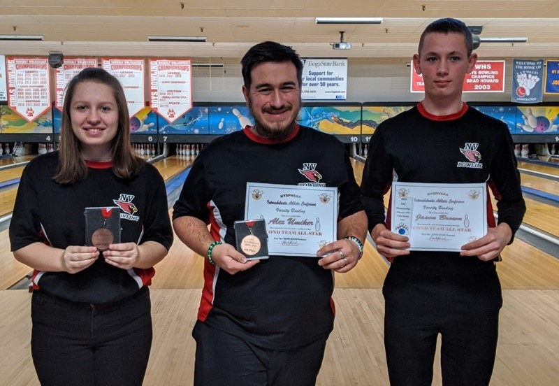One girl and two boys holding certificates and medals in bowling alley