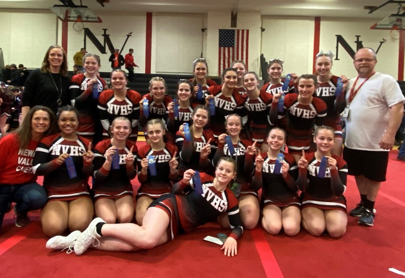 Girls cheerleading team with ribbons in gym