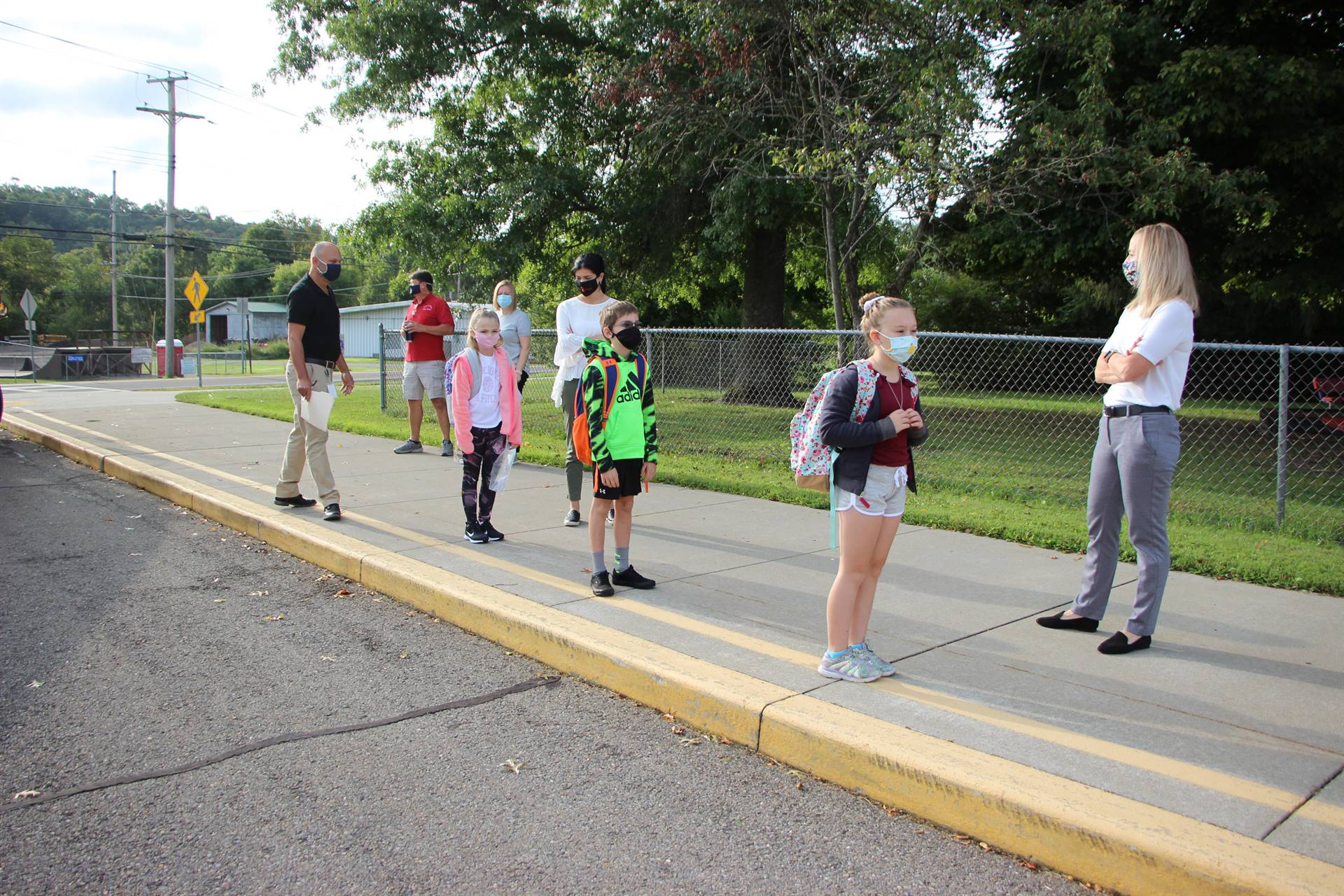 Three students stand on sidewalk next to teachers