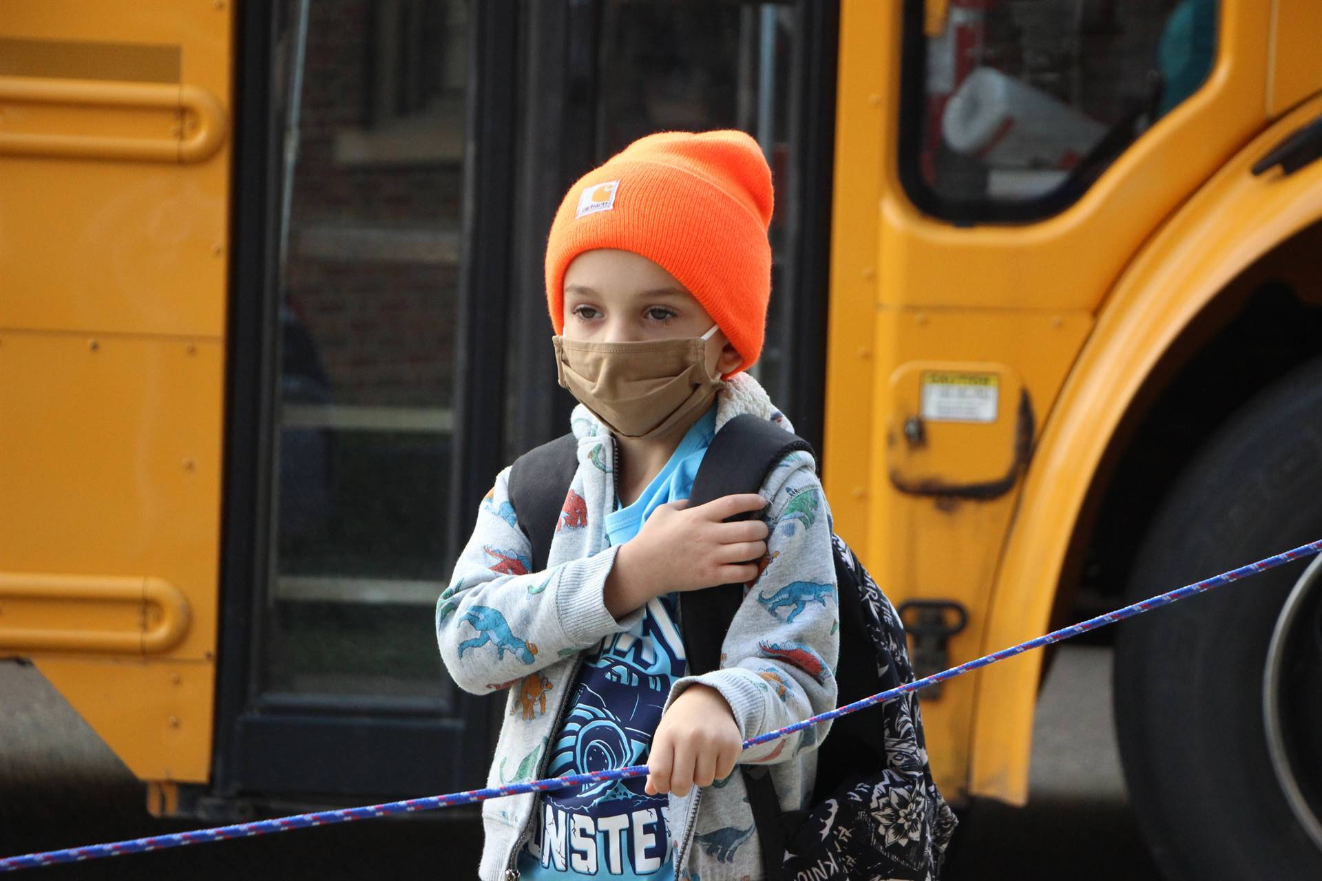 boy in facemask holding rope outside