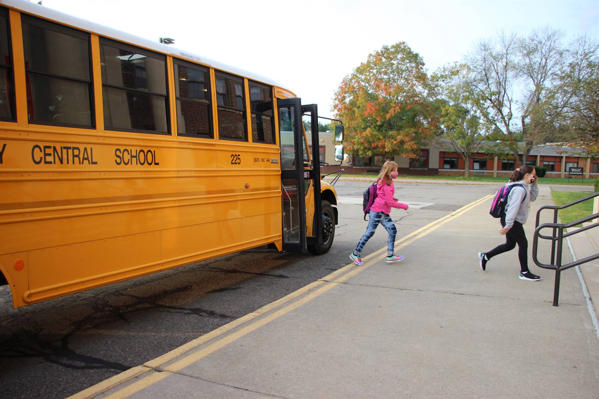 two girls getting off of school bus