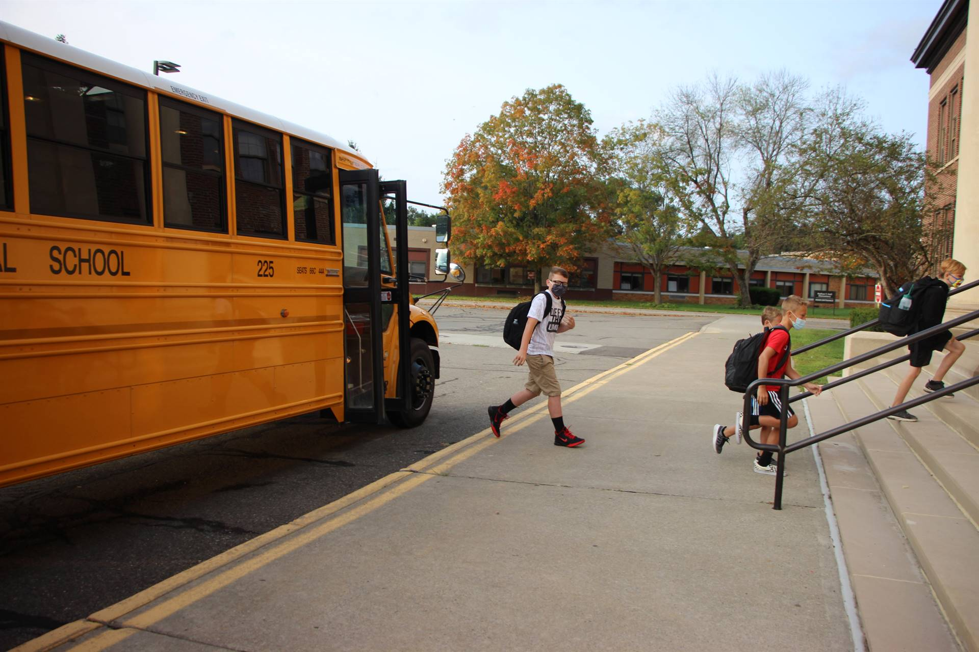 three boys getting off of school bus