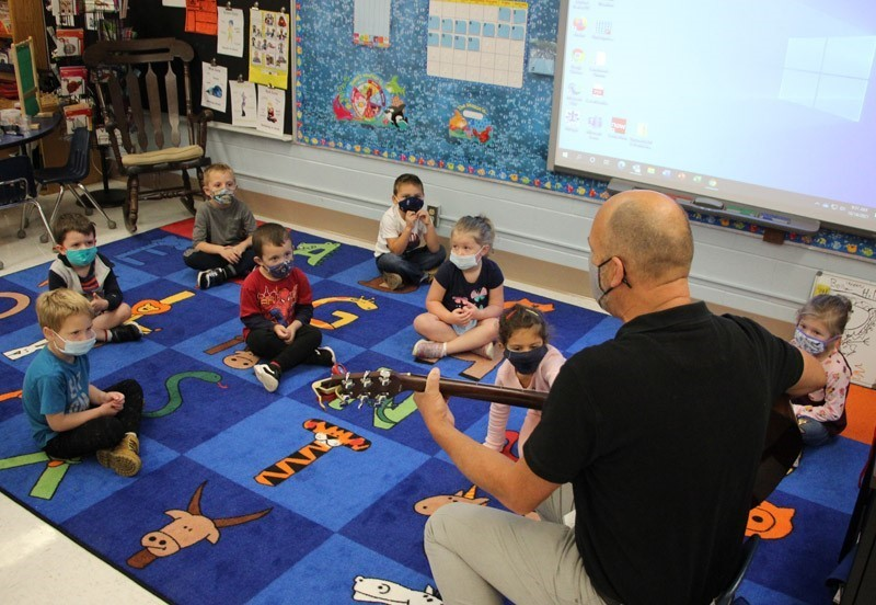 Pre-K students and principal with guitar