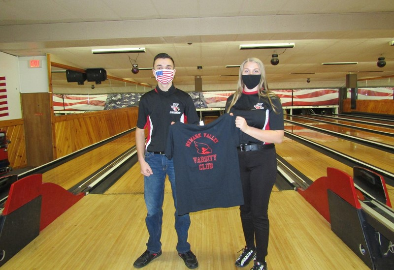 Boy and Girl holding T-shirt in a bowling alley